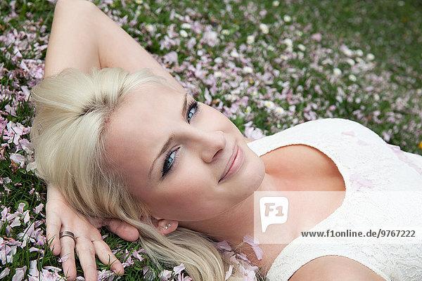 Blonde junge Frau liegt in einer Blumenwiese