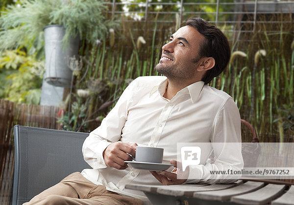 Dunkelhaariger Mann mit Kaffeetasse im Freien