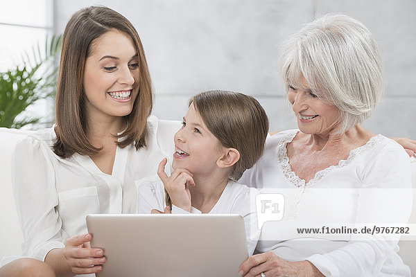 Grandmother  mother and daughter using laptop