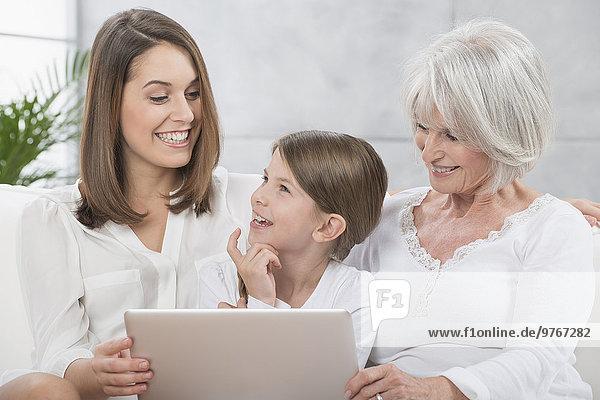 Großmutter  Mutter und Tochter benutzen einen Laptop