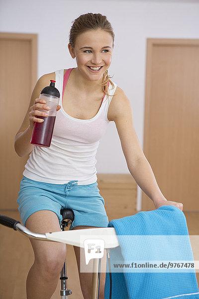 Junge Frau trainiert auf einem Fahrradergometer
