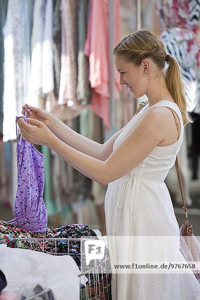 Frau an einem Geschäft sucht Kleidungsstücke aus