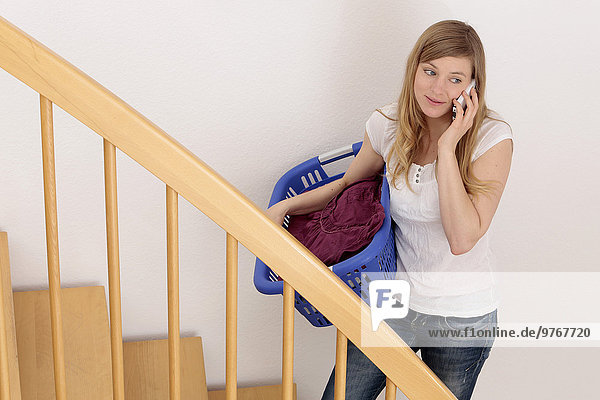 Frau auf der Treppe mit Wäschekorb und Handy