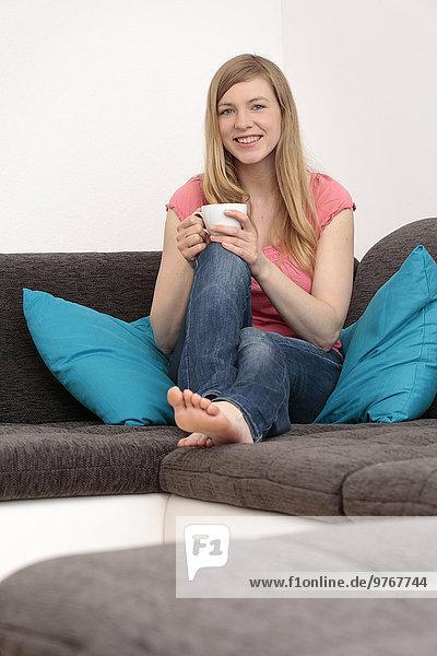 Lächelnde Frau mit Kaffeetasse auf der Couch