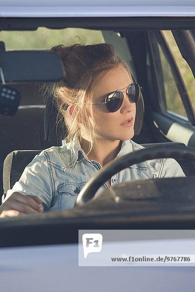 Attraktive blonde junge Frau sitzt im Auto