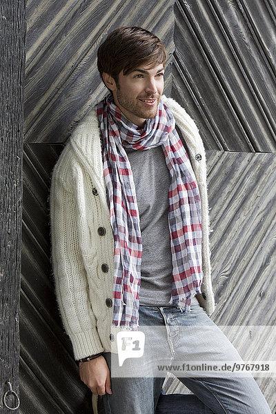 Lächelnder junger Mann mit Strickjacke