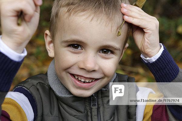 Fröhlicher Junge in herbstlichem Wald  Porträt