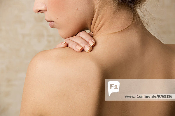 Junge Frau berührt ihren nackten Rücken