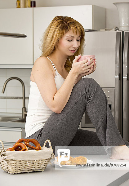 Junge Frau in der Küche trinkt Kaffee aus einem Becher