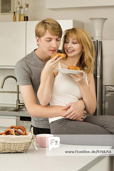 Junges Paar in der Küche mit Brezeln und Croissants