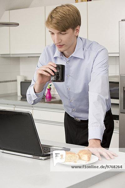 Junger Geschäftsmann benutzt einen Laptop in der Küche