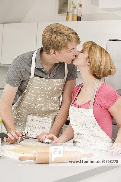Junges Paar küsst sich in der Küche