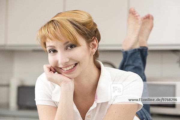 Lächelnde junge Frau mit der Hand am Kinn  Porträt