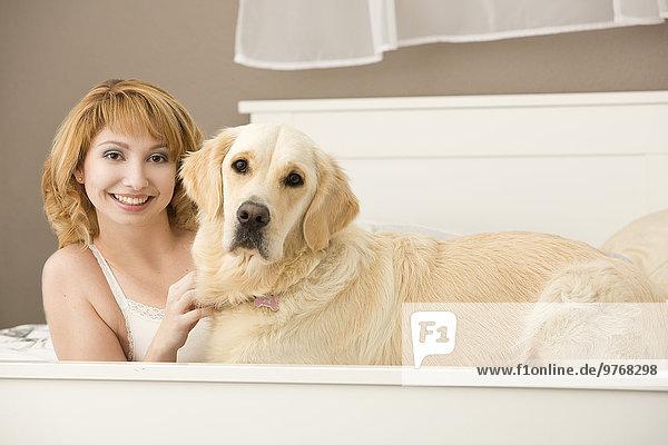 Junge Frau liegt mit einem Hund im Bett