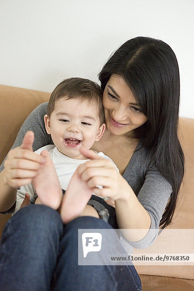 Mother and toddler sitting on couch