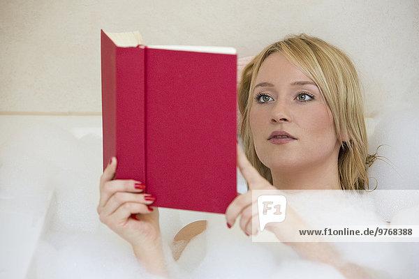 Blonde junge Frau liest ein Buch in der Badewanne