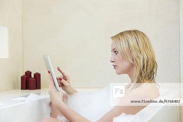 Blonde junge Frau mit Tablet-Computer in der Badewanne
