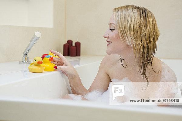 Blonde junge Frau mit Gummienten in der Badewanne