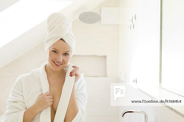 Junge Frau im Bademantel mit Handtuch um ihren Kopf gewickelt