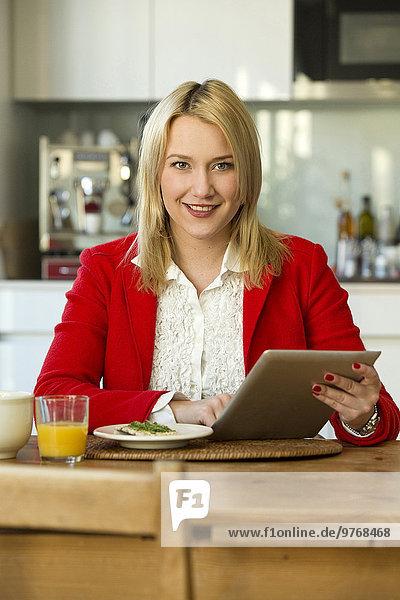 Blonde junge Frau in der Küche benutzt einen Tablet-Computer