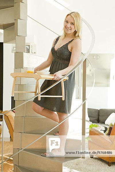 Blonde junge Frau im Negligé trägt ein Tablett auf einer Treppe
