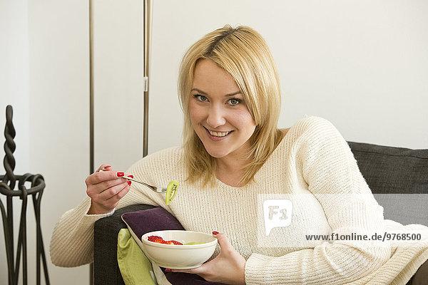 Blonde junge Frau im Wohnzimmer isst Obst