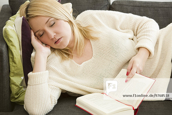 Blonde junge Frau im Wohnzimmer macht ein Nickerchen mit einem Buch in der Hand