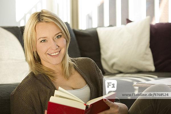 Blonde junge Frau im Wohnzimmer liest ein Buch