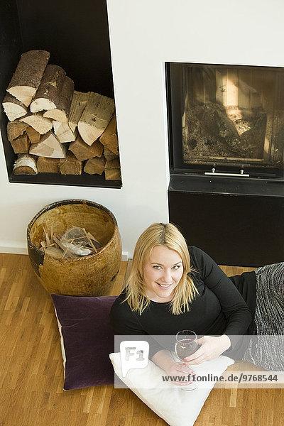 Blonde junge Frau liegt am Kamin mit einem Glas Rotwein
