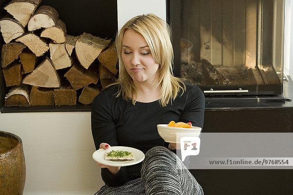Blonde junge Frau sitzt am Kamin mit Chips und Knäckebrot in ihrer Hand