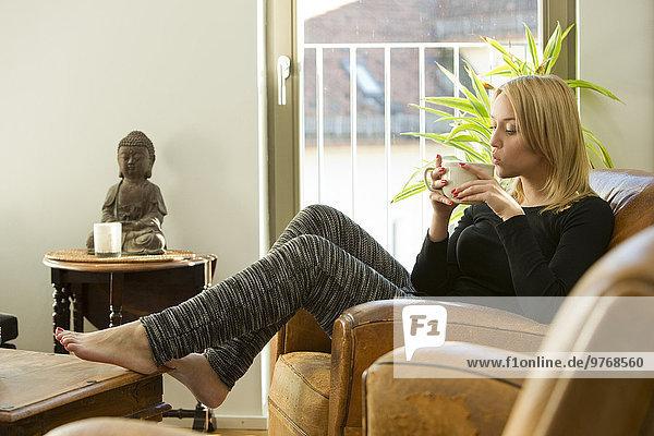 Blonde junge Frau im Sessel trinkt eine Tasse Tee