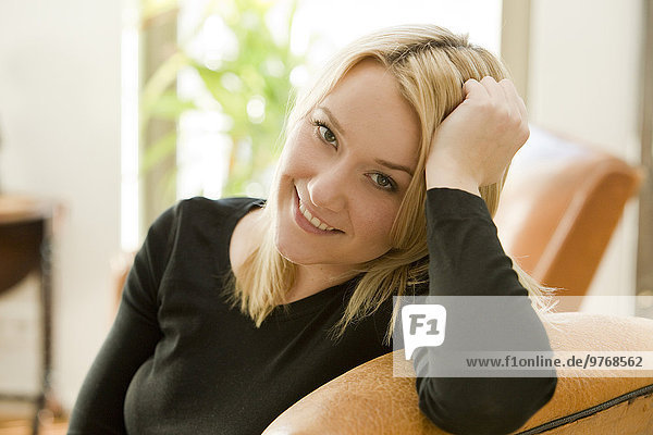 Blond young woman sitting in armchair  portrait