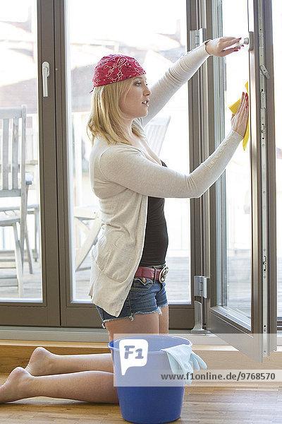 Junge Frau reinigt ein Fenster