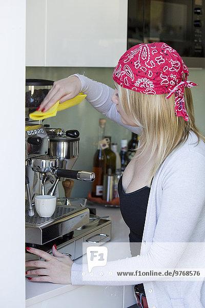 Junge Frau reinigt eine Espressomaschine
