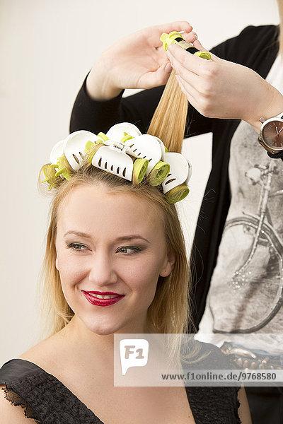 Junge Frau mit Lockenwicklern im Haar