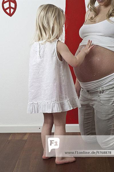 Tochter cremt den Bauch ihrer schwangeren Mutter ein