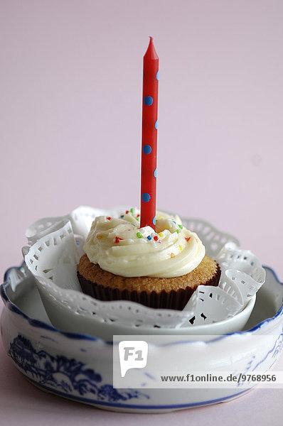 Garnierter Cupcake mit einer Geburtstagskerze