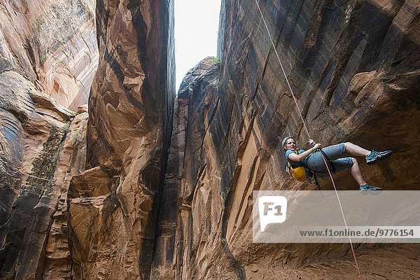 Woman rapelling down a giant arch  canyoneering  Moab  Utah  United States of America  North America