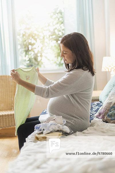 sitzend Frau sehen Bett Kleidung Schwangerschaft Baby