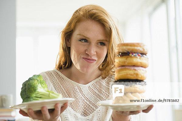 junge Frau junge Frauen halten Teller Donut Broccoli