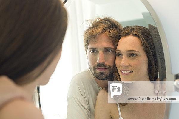 Paar  das zusammen in den Badezimmerspiegel schaut.