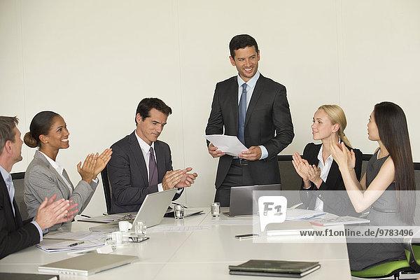 Führungskraft erhält Applaus von Kollegen bei der Präsentation