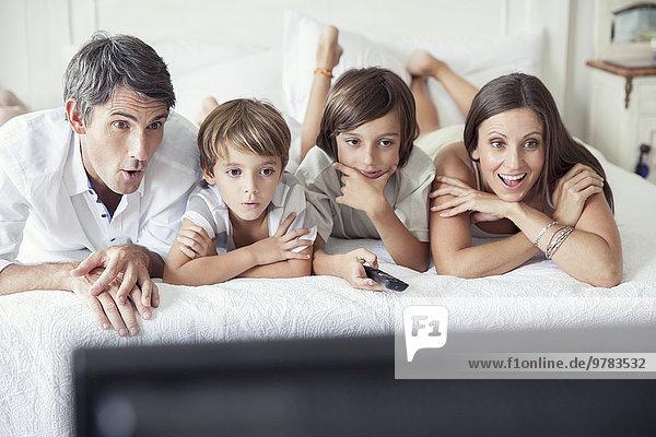 Familie beim Fernsehen im Bett  Porträt