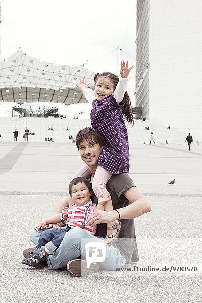 Vater sitzt auf dem Boden mit zwei Kindern auf dem Stadtplatz