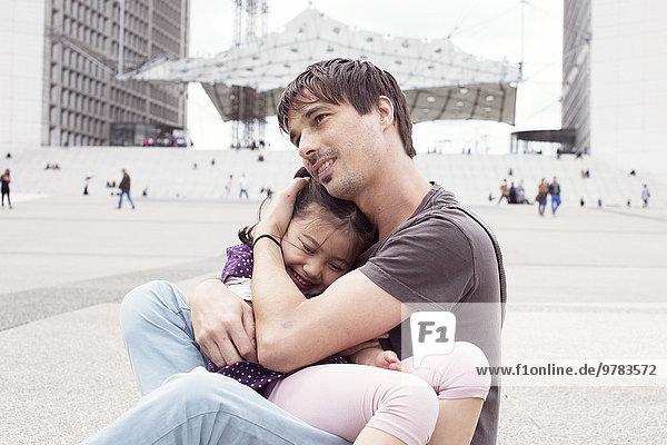 Vater hält junge Tochter auf dem Schoß im Freien