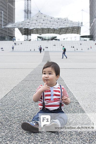 Kleiner Junge sitzt auf dem Boden auf dem Stadtplatz.