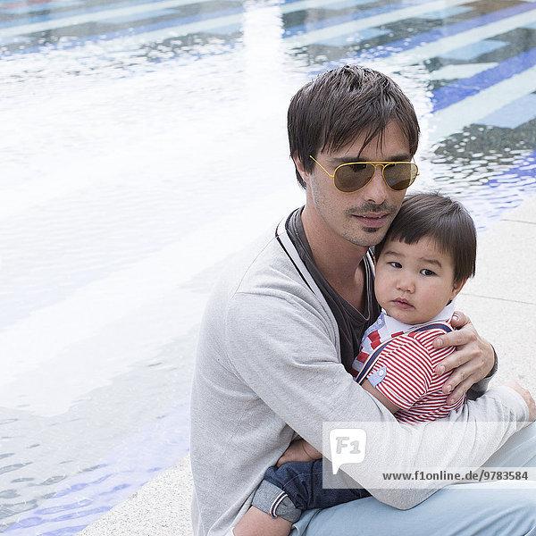 Vater hält jungen Sohn auf dem Schoß im Freien