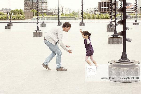 Vater und Tochter spielen zusammen im Stadtpark