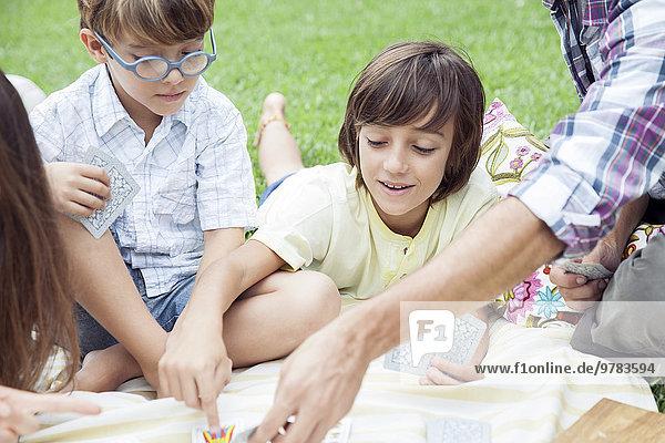 Jungen spielen Karten beim Familienpicknick