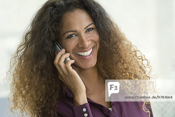 Woman talking on cell phone  smiling cheerfully